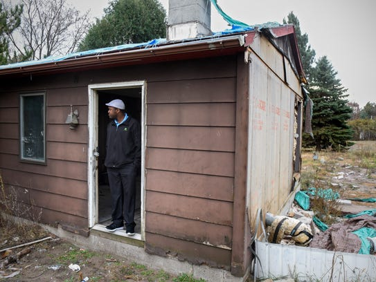 Mike Nwachukwu stands in a doorway of a small building