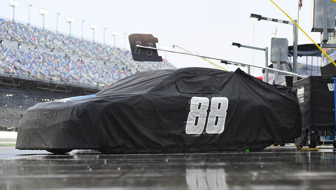 Dale Earnhardt Jr.'s car sits covered on pit road during a weather delay before the Coke Zero 400 at Daytona International Speedway.