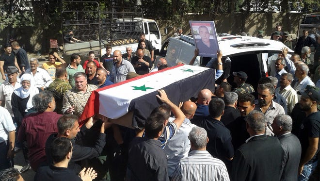 In this photo released by the Syrian official news agency SANA, mourners carry a coffin of more than 200 people who were killed a day earlier by a series of suicide bombings launched by the Islamic State's fighters on the eastern and northern countryside of the southern province of al-Sweida during a mass funerals in al-Sweida, Syria, Thursday, July 26, 2018.