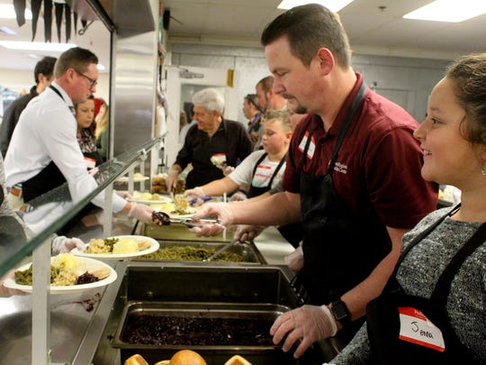 Jenna Colgate, right, and other volunteers make and hand out plates Wednesday during the Good News Rescue Mission's Great Thanksgiving Banquet.