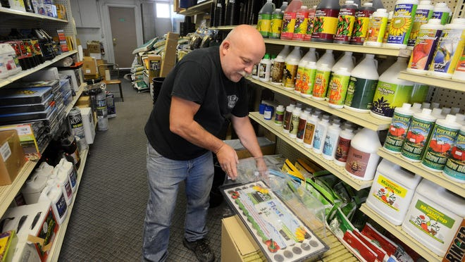 Russ Olson, owner of Steins and Vines, shows a basic hydroponics kit he sells for starting seeds in his store at 2307 W. Madison St.