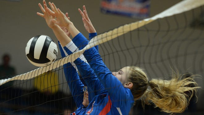 Union County's Sydney Bradford and Ella Dils jump at the net in the volleyball regional Tuesday, Oct. 27, 2015 at Union County High School in Liberty.