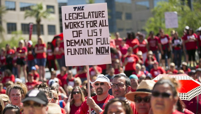 Dave Price, a social studies teacher at Mesa Public Schools, holds a sign during a rally during the sixth day of the Arizona teacher walkout at Wesley Bolin Memorial Plaza near the Arizona state Capitol in Phoenix on Thursday, May 3, 2018. Today will likely be the final day of the walkout as Governor Ducey signed an education funding bill into law early Thursday morning.