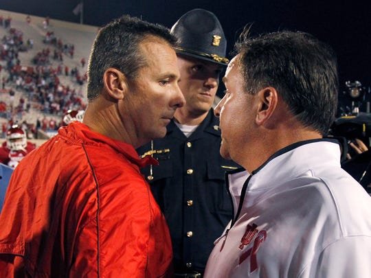 Then-IU coach Kevin Wilson, right, and Ohio State coach Urban Meyer talk after Ohio State's 52-49 win in 2012. They now coach together.