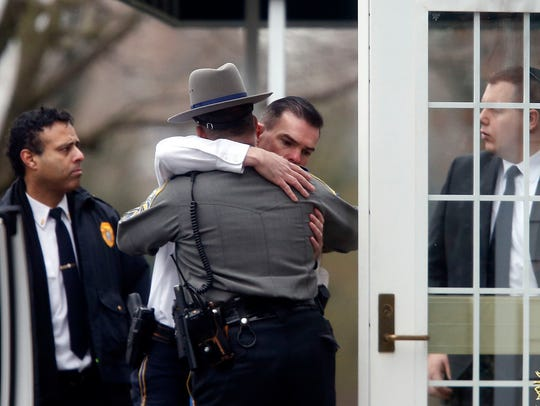 Police officers comfort one another outside a funeral