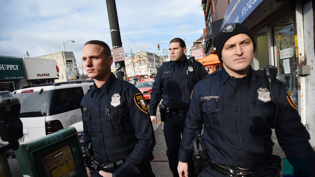 Three Paterson police officers patrol in the commercial shopping district in downtown Paterson.