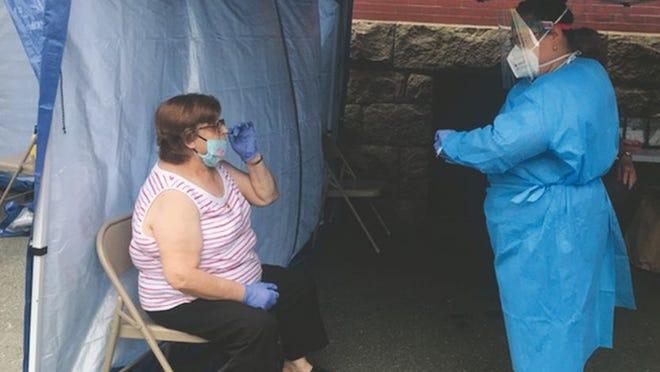 Um membro da equipa da Seven Hills Behavioral Health prepara-se para fazer um teste gratuito à Covid-19 a uma senhora, na passada segunda-feira, junto ao Centro de Assistência ao Imigrante.