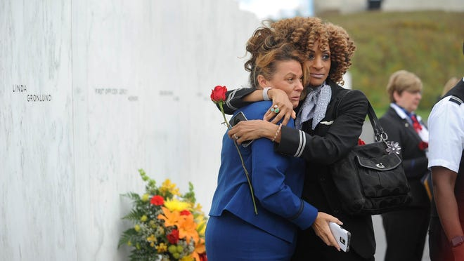 United Airlines flight attendants Clarice Rinker, left, and Janeen Brown embrace at the Wall of Names on the Memorial Plaza at the Flight 93 national memorial near Shanksville, Pa., Sunday, Sept.11, 2016, on the 15th anniversary of the terror attacks. Their fellow flight attendants, pilots and servers were killed when Flight 93 crashed in a field near Shanksville. (John Rucosky/Tribune-Democrat via AP)