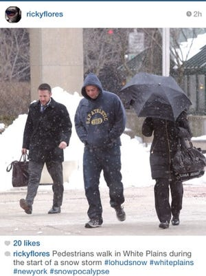 Pedestrians walk in White Plains during the start of a snow storm Jan. 26.