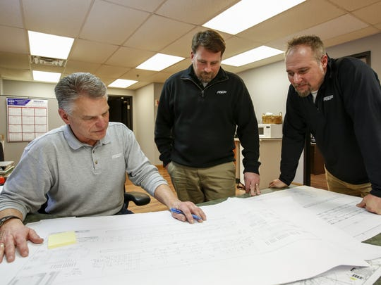 AT&F engineers Jack Herrmann, Dan Amann and Todd Gilbert go over fabrication plans for a railcar company Feb. 7 in Manitowoc