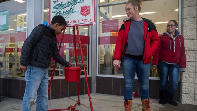 Jordan Anthony, 9, donates money to the Salvation Army as Cara Duncan (left) and Courtney Williams spend their two-hour volunteer shift ringing the bell outside K-Mart in Henderson on Monday afternoon.