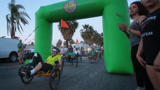 A couple of hand cycles lead the Palm Springs Cycledelic night bicycle ride on Thursday in Palm Springs.