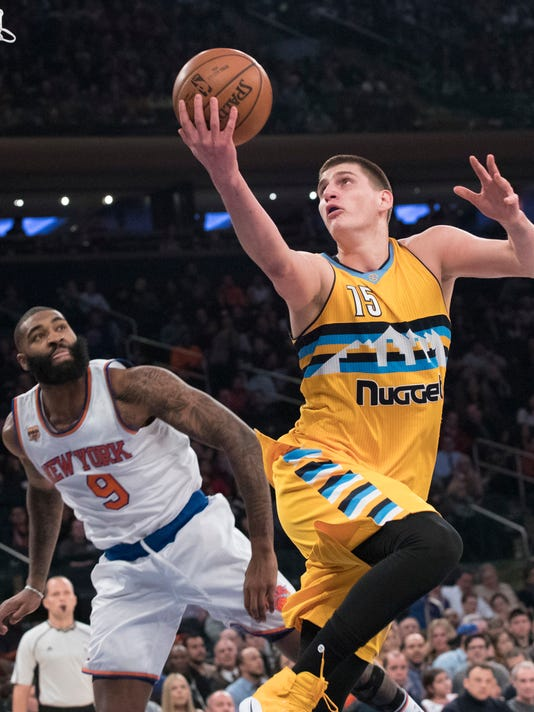 Denver Nuggets forward Nikola Jokic (15) goes to the basket past New York Knicks center Kyle O'Quinn (9) during the first half of an NBA basketball game, Friday, Feb. 10, 2017, at Madison Square Garden in New York. The Nuggets won 131-123. (AP Photo/Mary Altaffer)