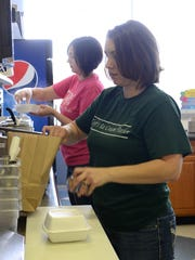 Heather Keegan prepares a sandwich as Amber Keiser bags food for a customer at Tofts on Tuesday, Sept 30, 2014.
