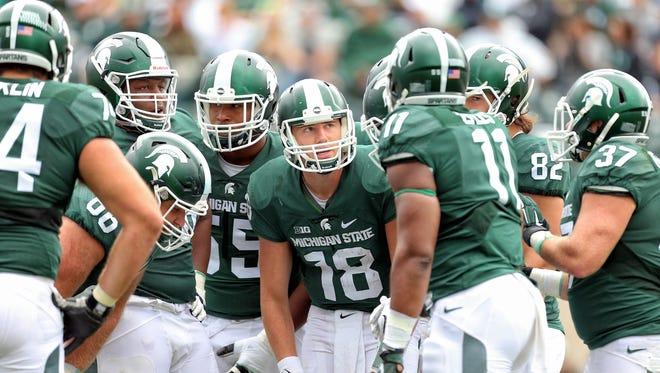 Sep 19, 2015; East Lansing, MI, USA; Michigan State Spartans quarterback Connor Cook (18) call a play in the huddle during the 2nd half of a game at Spartan Stadium. MSU won 35-21.
