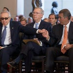 Senate Minority Leader Harry Reid (L) shakes hands with Speaker John Boehner (R), as Senate Majority Leader Mitch McConnell (C) looks on, during a ceremony held to commemorate the 50th anniversary of the Vietnam War.