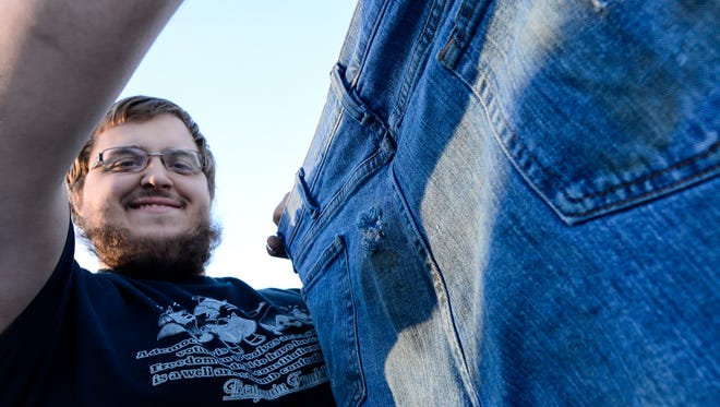 Jeremy Dettinger holds up the jeans he was wearing when he was shot Oct. 26, 2015 outside his parent's home in North Codorus Towship.  Monday January 25, 2016. (John A. Pavoncello - The York Dispatch)