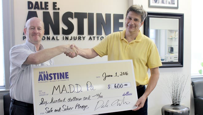 Malcolm Friend, left, program manager of Mothers Against Drunk Driving PA, accepts a $600 check from Greg Martin, personal injury attorney, Dale E. Anstine.