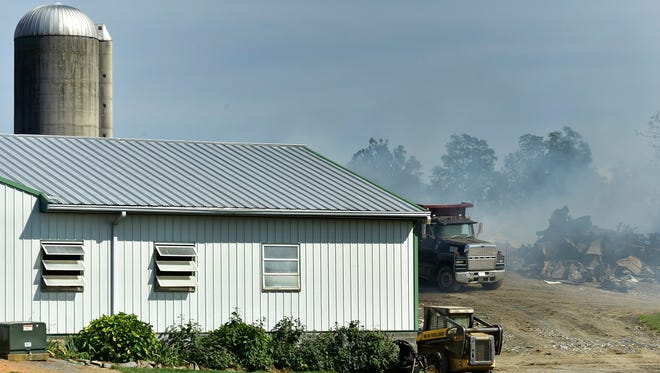 Smoke billows from the remains of a barn fire that occurred overnight on a long lane of Bukholder Road in Antrim Township.