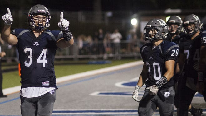 Dallastown's Benjamin Ward, left, points into the crowd after scoring a touchdown. Dallastown defeats Spring Grove 52-13 in football at Dallastown Area High School, Friday, September 22, 2017.