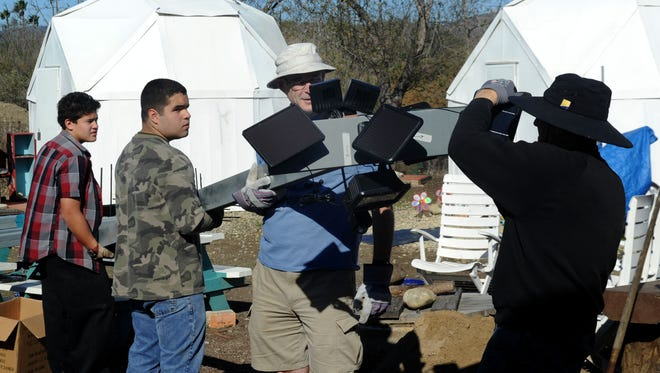 From left are Adam Argueta, a freshman at Buena High School; Nathan Martinez, a junior at Buena; Richard Smith, a teacher at Buena; and Al Geller, a volunteer from Temple Beth Torah in Ventura. They were working on setting up a post with solar lighting at River Haven.