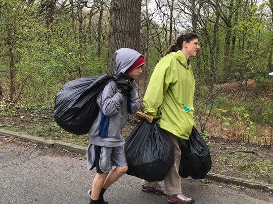 Eli Fellus, 11, helps his mom Ruth Borgenicht carry some collected litter out of Toney's Brook in Montclair April 22, 2017.