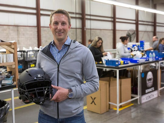 Ryan Sullivan, President of Xenith, poses for a photograph with a helmet at the Xenith factory on Tuesday, April, 25, 2017 in Detroit. Xenith makes high-tech football helmets, shoulder pads and other safety equipment.