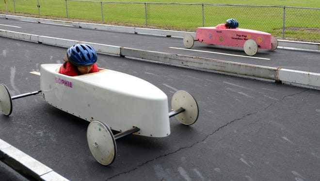 Sophie Maynard-Tkaczuk, left, and Jessie Mayne race down the hill at Derby Downs in Lancaster Saturday, June 27, 2015, during the Lancaster Soap Box Derby .