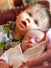 Trevor Gassman, 2, snuggles with his sister Aubrey,