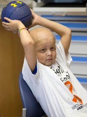 Brody Stephens, 7, holds a basketball while watching television at Riley Hospital for Children, Wednesday, July 13, 2016.