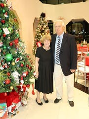 Rick and Janice Hunger, longtime supporters of CASTLE, stand near one of the live auction Christmas trees at the Nov. 18 gala.