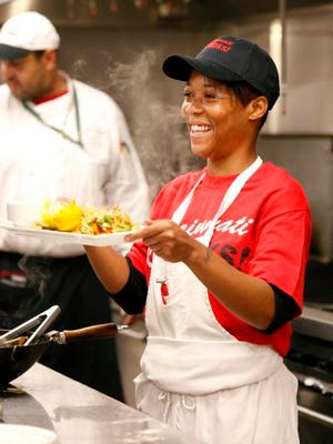 Robin Woodard smiles as she shows off a stir-fry dish she prepared during her Cincinnati Cooks class, a ten-week program provided by the Freestore Foodbank, on Wednesday morning.
