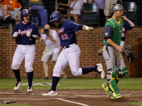 Vanderbilt's Zander Wiel (43) scores the winning run as Oregon catcher Jack Kruger, right, walks away from the plate in the bottom of the ninth inning Sunday. Wiel scored from third on a pinch-hit single by Ro Coleman.