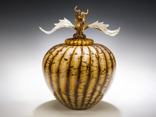 A batik covered sphere with avian finial is from Danielle Blade and Stephen Gartner. In their Strata collection of vases and vessels, tones of warm, earthy color are blown into layers that evoke geological terrain.