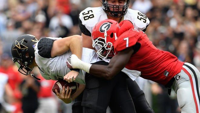 Oct 15, 2016; Athens, GA, USA; Vanderbilt Commodores quarterback Kyle Shurmur (14) is sacked by Georgia Bulldogs linebacker Lorenzo Carter (7) during the second quarter at Sanford Stadium.