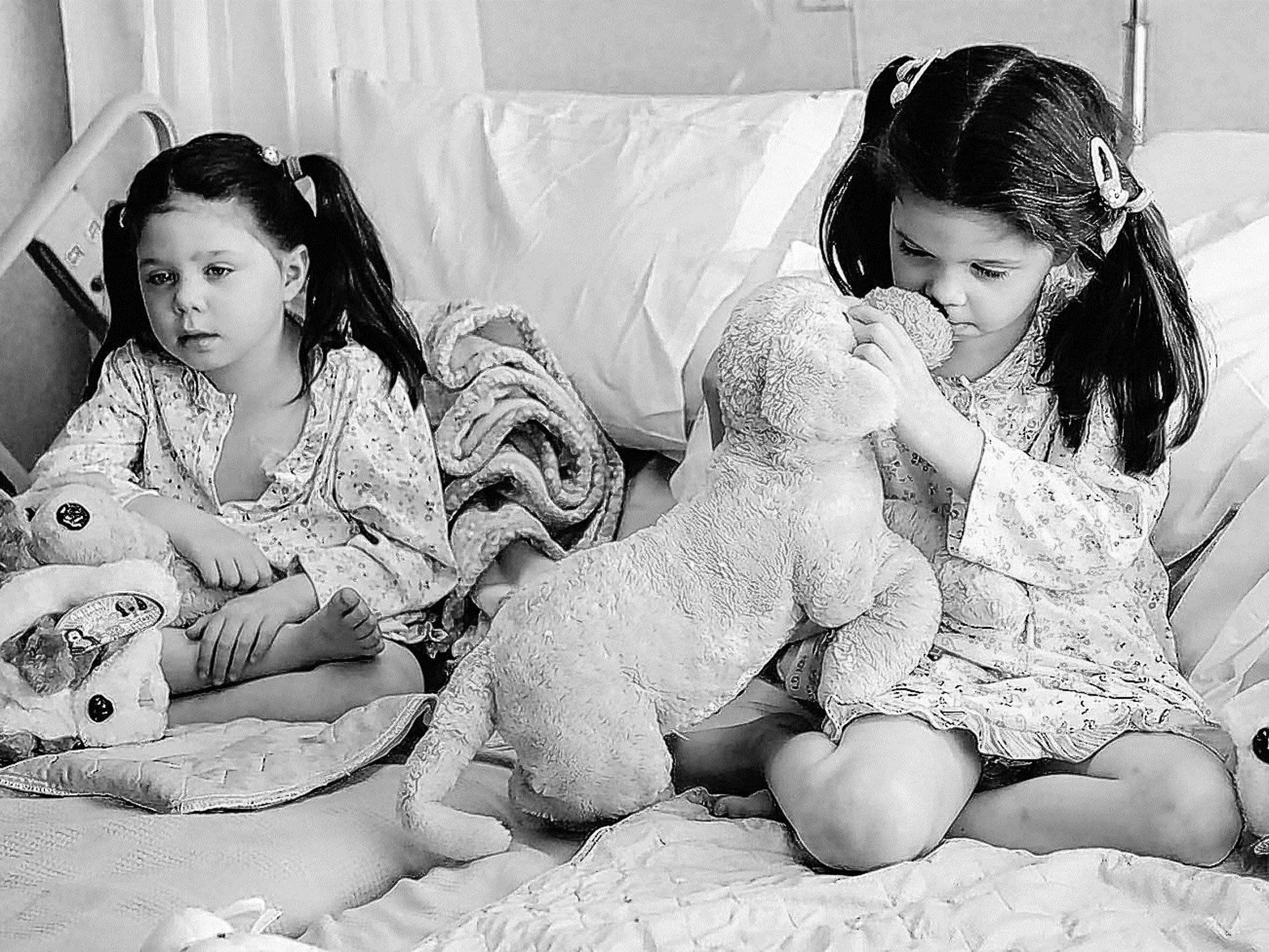 Twins Addi, left, and Cassi Hempel wait in their Renown Regional Medical Center hospital beds in 2009 for infusion pumps to be attached to ports
