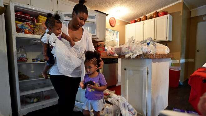 Dolecia Cody puts away groceries in her aunt's home alongside her children, 10-month-old Jamari Cody, and 2-year-old Jakayla Hudson.