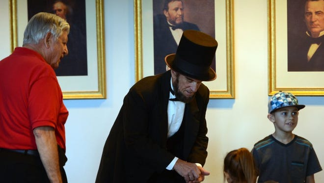 KAREN QUINCY LOBERG/THE STAR Dennis O'Hanlon (left) a docent, waits to lead J.P. Wammack, embodying the role of Abraham Lincoln, on stage but waits as he gives pennies out to Taylor Abernathy and her brother Ryan Abernathy on Monday at the Ronald Reagan Presidential Library and Museum in Simi Valley. Abigail Adams, Theodore Roosevelt, Thomas Jefferson and George Washington were among other historic figures represented by actors for the annual Presidents Day celebration.