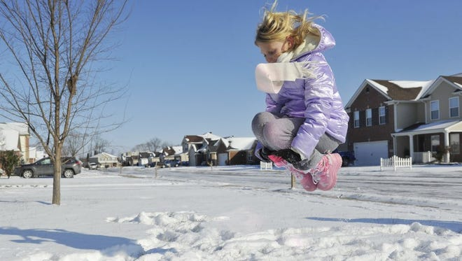 Kayla Allen, 9, jumps into a pile of snow she made while playing with her siblings at their home in Newburgh while enjoying their snow day.  Jan. 11, 2016.