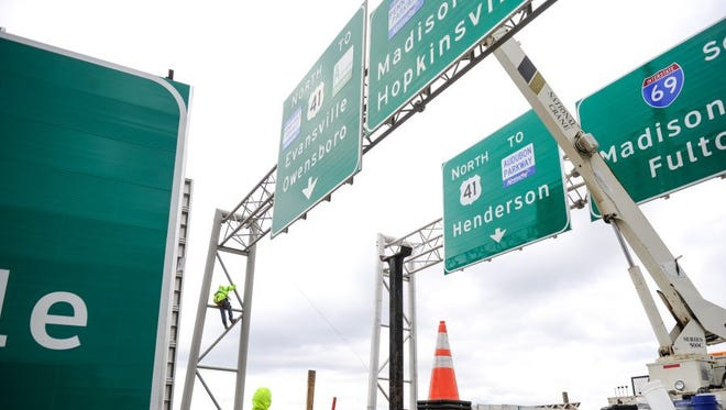 Jerry Hack (left) holds a guide rope as Robby Merrifield operates the boom truck while dismantling the old road signs after installing new and reworded signs at the Kentucky 425/South Bypass interchange with Interstate 69 in Henderson in this December, 2015, file photo. From this intersection and continuing south, the Pennyrile is now designated I-69.