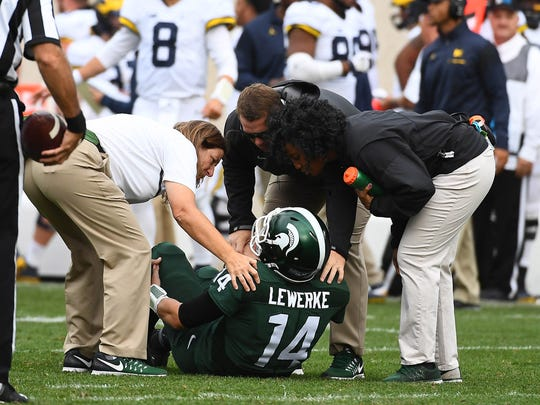 Michigan State quarterback Brian Lewerke (14) grabs his leg after suffering a broken left tibia late in MSU's loss to Michigan on Oct. 29.