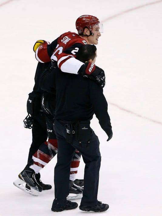 Arizona Coyotes' Michael Stone is helped off the ice after injuring his leg during the third period of an NHL hockey game against the Philadelphia Flyers on Saturday, March 26, 2016, in Glendale, Ariz. The Coyotes defeated the Flyers 2-1. (AP Photo/Ross D. Franklin)