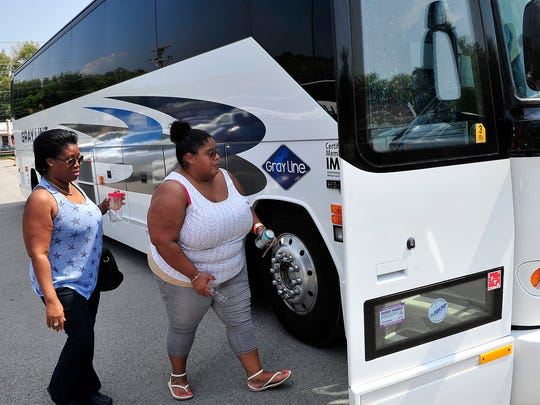 Charmaine Alleyne, left, and Maria Sifre, both of New York,  walk to an awaiting bus to try food from the participating restaurants in the Nolensville Pike area during the 3rd Annual InterNASHional Food Crawl.