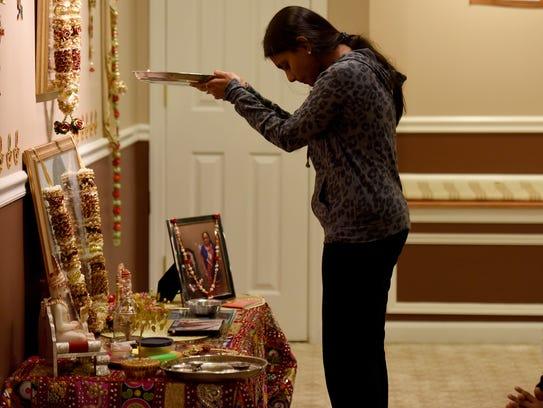 Chaitali Shah prays before the altar with a ghee lamp