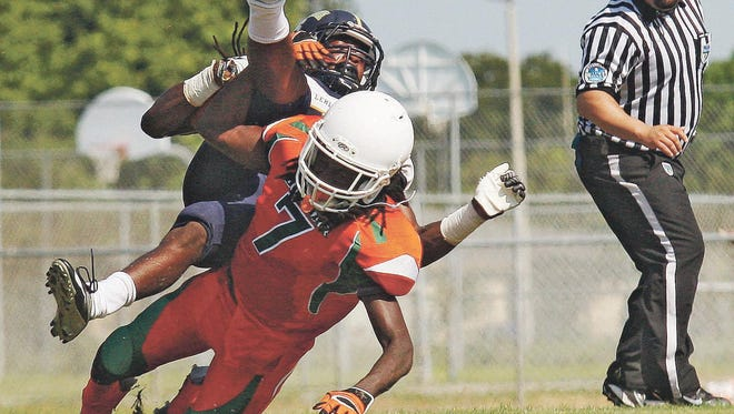 Lehigh High School's Henry Shackleford, toop, is tackled by a Dunbar defender Saturday at Dunbar High School in Fort Myers.