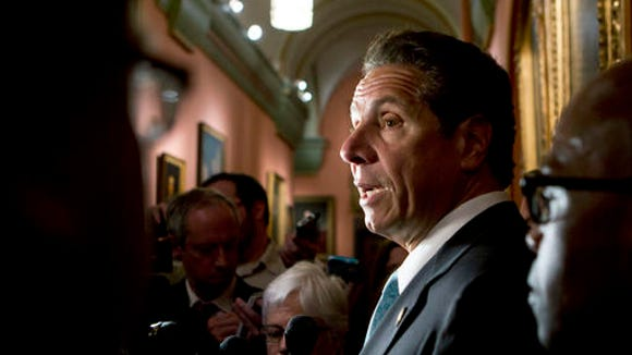 New York Gov. Andrew Cuomo talks to media members outside his office at the state Capitol on Tuesday, May 24, 2016, in Albany, N.Y. Cuomo says tightening campaign finance laws and fighting the heroin epidemic are two of his top priorities as lawmakers near adjournment.