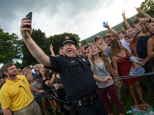Lt. Fred Raub of the Endicott Police interacts with concert-goers before performances by The Cadillac Three and Florida Georgia Line at the Dick's Sporting Goods Open.