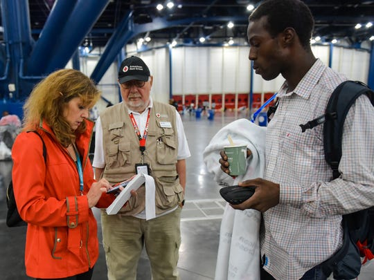Kris Wartelle helps Evacuee RJ Ellis gets a dry pair of socks at the George R. Brown Convention Center downtown Houston, TX. Monday, Aug. 28, 2017.