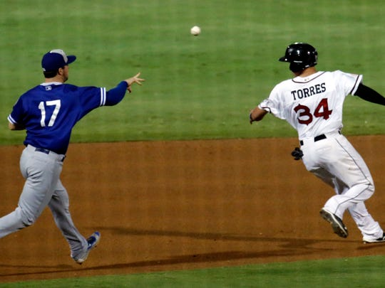 El Paso Chihuahuas outfielder Nick Torres gets caught in a rundown between second and third base as the Oklahoma City Dodgers' third baseman prepares to tag Torres out.