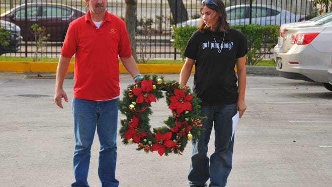 Chris Melton and Karen Brown carry a wreath at a December memorial service for homeless individuals who passed away in Brevard County in 2016. The North Brevard Charities Sharing Center and the Daily Bread in Melbourne traditionally hold the ceremony on the first day of winter, the longest night of the year.